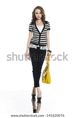 Full length young woman with yellow bag walking in studio        - stock photo