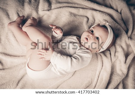 Full lenth body of little baby girl lies on blanket