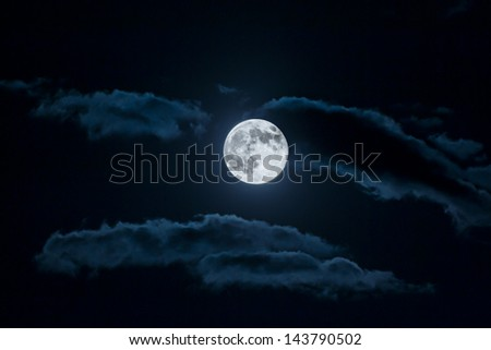 Full moon and white clouds on black night sky - stock photo