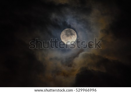 Full moon behind clouds, with visible details on it's surface