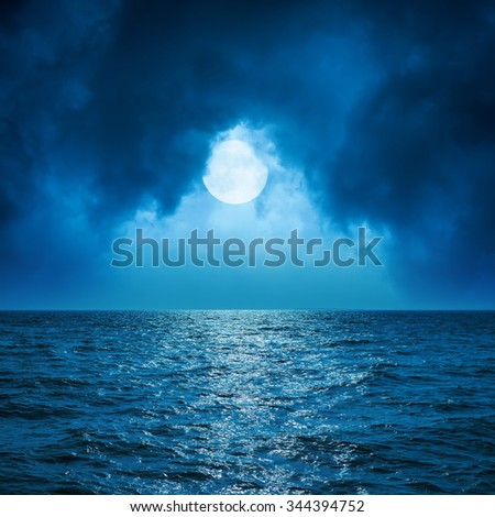 full moon in clouds over dark blue sea - stock photo
