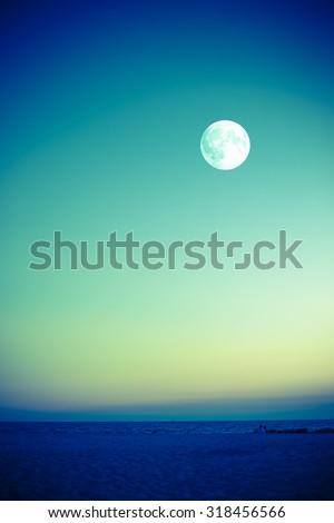 Full moon over beach at dusk - stock photo