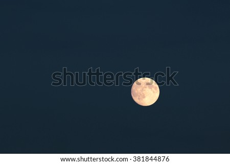 Full moon over cloudless dark blue night sky