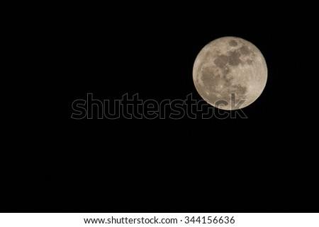 Full moon over dark black sky at night - stock photo