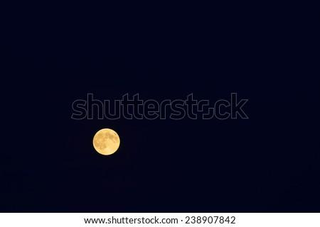 Full moon over dark blue sky. Gold full moon. Late summer. Poland.  - stock photo