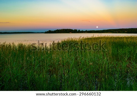 Full moon over lake in late evening. Reeds in foreground and distant cabins on opposite shore. Calm water and fine sky. - stock photo