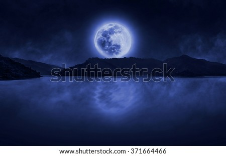 Full moon over the dam with clouds and fog on water skin - stock photo