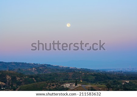 Full moon perigee over colorful shade twilight during sunrise - stock photo