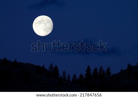 Full Moon rises over the Cascade Mountains, in north central Washington State, home of some of the United States' darkest night skies, and the alleged home of Bigfoot / Sasquatch Midnight Blue Sky - stock photo