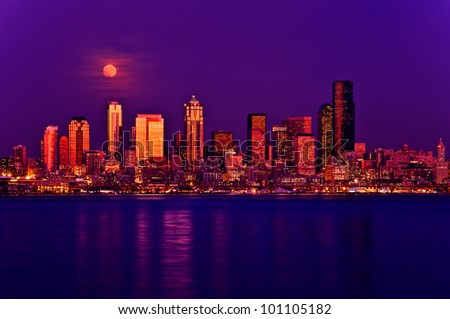 Full moon rising above Seattle city skyline.