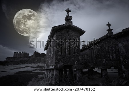 Full moon rising at dusk over the medieval castle and old granite corn barns from remote village of Lindoso, north of Portugal. Used analog infrared filter andl digital filters. Illustration. - stock photo