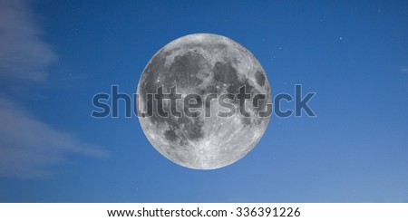 Full moon seen with an astronomical telescope over the blue sky with stars (taken with my own telescope, no NASA images used) - stock photo