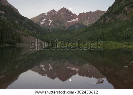 Full moon setting over the Maroon Bells in Colorado's Rocky Mountains, reflected in Maroon Lake, near Aspen. - stock photo