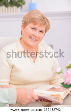 Full of happiness. Pleasant adult content woman sitting on the sofa and holding photo album while looking through it with her husband - stock photo