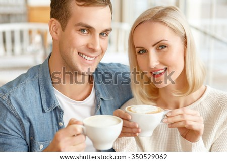 Full of joy. Pleasant content smiling couple sitting in the cafe and drinking coffee while feeling glad