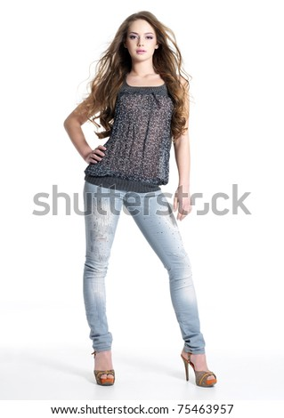 Full portrait of beautiful stylish girl in fashion stylish jeans posing - isolated on white background.  Fashion model posing at studio. Full length portrait - stock photo
