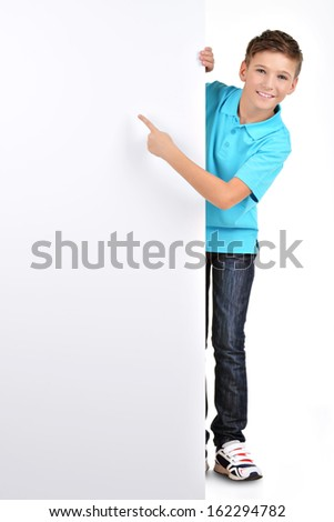 Full portrait of  cheerful boy pointing on white banner - isolated on white background - stock photo