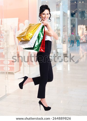 Full portrait of happy woman with color shopping bags standing in the shop. - stock photo
