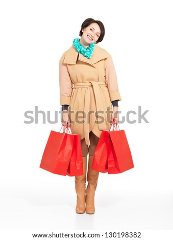 Full portrait of happy woman with shopping bags in autumn coat with green scarf standing isolated on white background