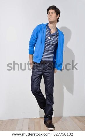 Full portrait of man posing on wooden background - stock photo