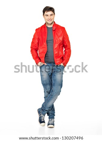 Full portrait of smiling happy handsome man in red jacket, blue jeans and gym shoes. Beautiful guy standing  isolated on white background - stock photo