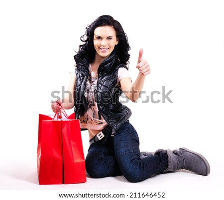 Full portrait of smiling woman with red shopping bags sitting on the floor -  isolated on white. - stock photo