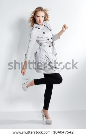 Full portrait of young beautiful fashionable woman in a gray coat and silver high heels shoes - series of photos