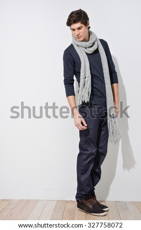 Full portrait of young man with scarf in studio - stock photo