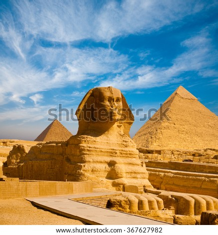 Full profile of Great Sphinx including pyramids of Menkaure and Khafre in the background on a clear sunny, blue sky day in Giza, Cairo, Egypt with no people - stock photo