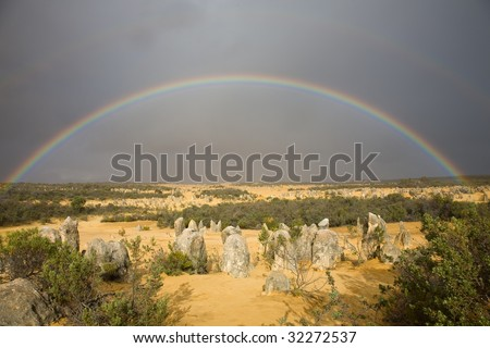 Full rainbow over pinnacles national park. Dark sky and rainbow over the yellow sand create a great atmosphere. - stock photo