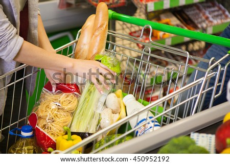 Full shopping cart at store with fresh products. - stock photo