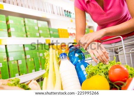 Full shopping cart at store with fresh vegetables and hands close-up. - stock photo