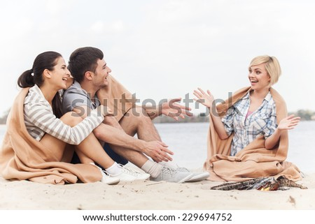 full view of happy friends having fun around bonfire. three friends sitting under blanket and warming near fire - stock photo