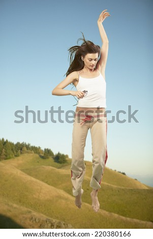 Full view of woman jumping in air while listening to music - stock photo
