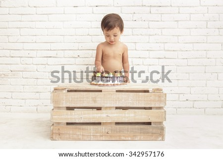 full view portrait of handsome toddler playing with his cake - stock photo