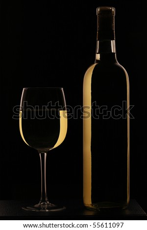 Full wine glass of white wine with bottle against black background - stock photo