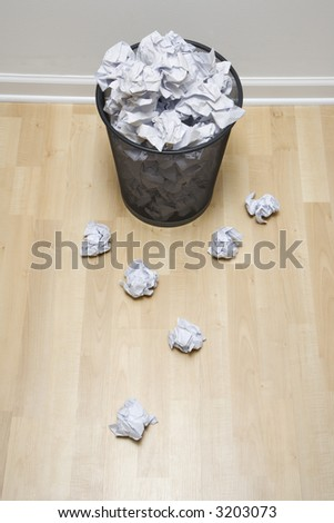 Full wire mesh trash can with crumpled paper scattered around. - stock photo