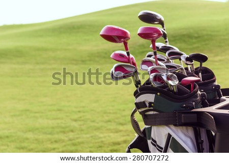 Fully equipped. Close up of bag full of different golf clubs on background of green course. - stock photo