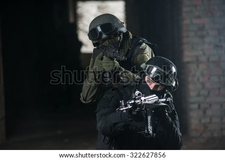 Fully equipped military men with automatic weapons playing in  airsoft strikeball - stock photo