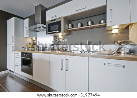 fully fitted modern kitchen with decorative elements - stock photo