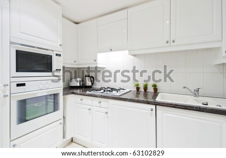 fully fitted white kitchen with stone worktop - stock photo