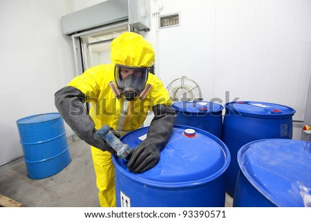 fully protected in yellow uniform,mask,and gloves professional dealing with chemicals - stock photo