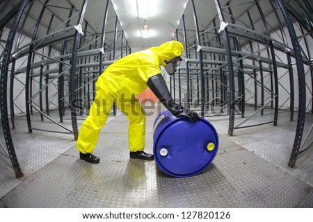 fully protected in yellow uniform,mask,and rubber gloves technician,rolling the barrel with toxic substance in empty warehouse - fish eye lens - stock photo