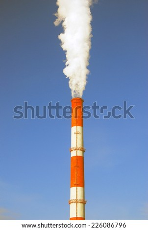 Fuming tube. Blue sky background. - stock photo