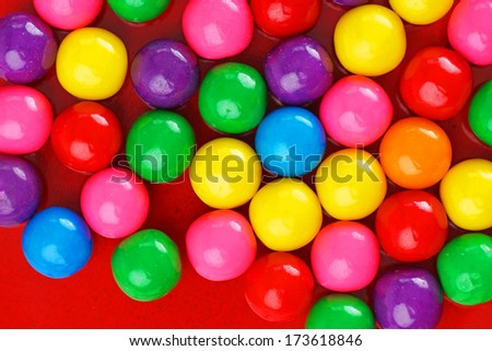 Fun and colorful gumball or bubble gum background on red ceramic - stock photo