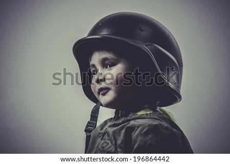 fun and funny child dressed in military cap, playing war games