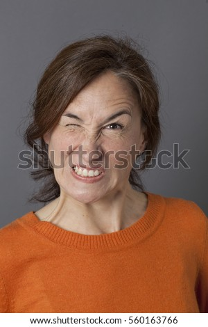 fun angry expression for winking middle aged woman showing her teeth for mother's exasperation and crazy frustration, grey background
