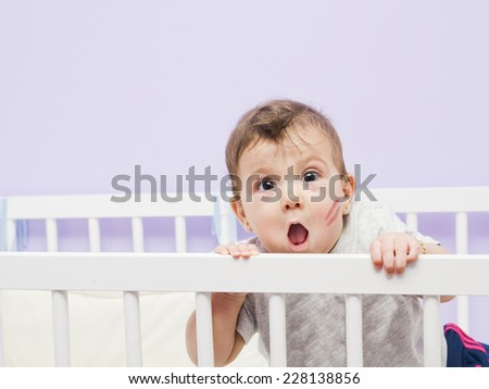 Fun baby with kiss mark on cradle in home bedroom. - stock photo