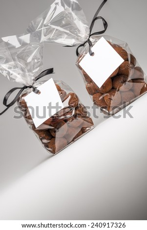 Fun Christmas gifts. Two luxury plastic bags with black ribbons of chocolate truffles and copy space. Blank label  that you can add your own trademark or your own message. Shooting in studio. - stock photo