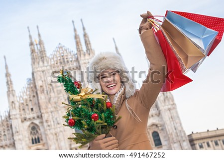 Fun Christmas trip to Milan, Italy. happy young traveller woman in Milan, Italy with Christmas tree and shopping bags rejoicing